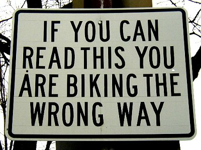 Sign on a street in Cambridge, MA reading: IF YOU CAN READ THIS YOU ARE BIKING THE WRONG WAY.