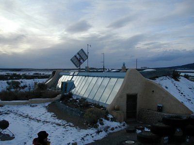Earthship, outdoor view showing solar panels, outside of Taos, New Mexico.