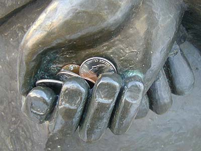 Coins in St. Francis' hands.