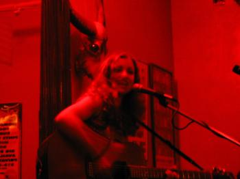 Woman playing guitar under red light, with a glowing-eye skull behind her head, at a bar on the Upper East Side.